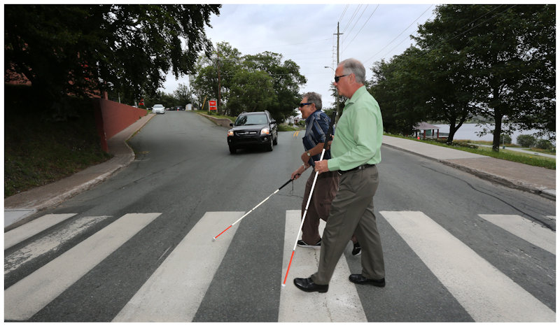 Men with canes crossing at a cross walk