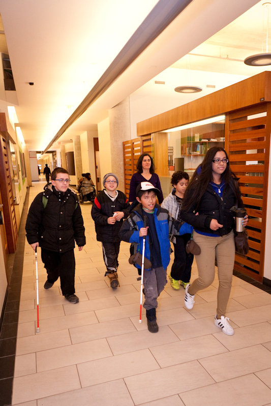 CNIB camp kids with canes leaving the office walking down the corridor.
